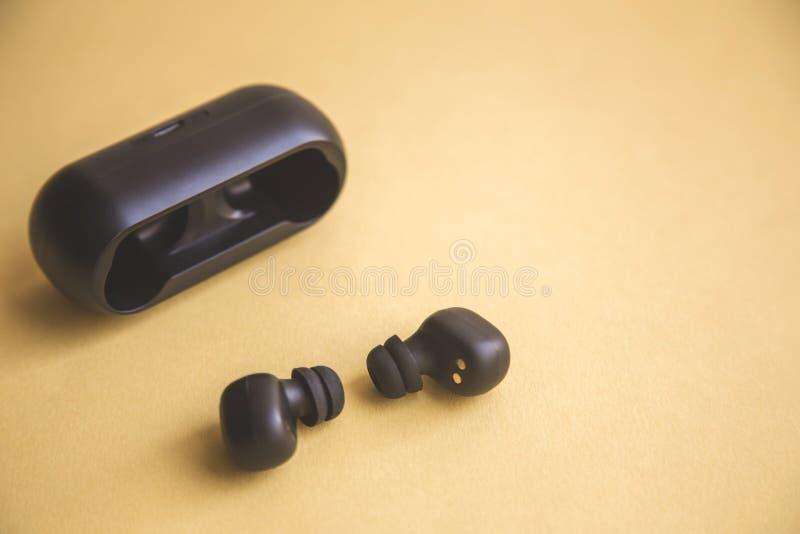 Écouteurs sans fil noirs avec le microphone sur le fond jaune image libre de droits