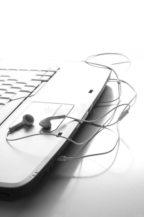 Écouteurs sur l'ordinateur portatif image stock