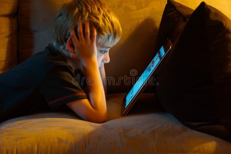 Écran d'ordinateur de observation de jeune garçon image libre de droits
