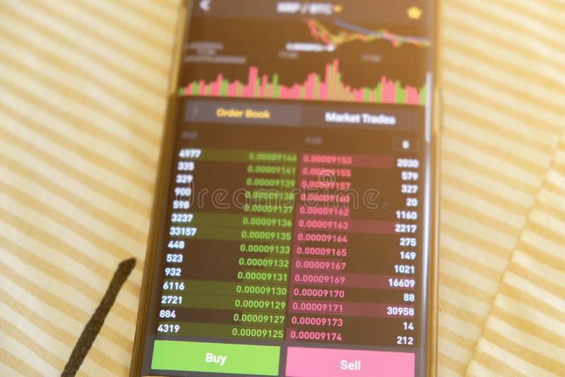 Écran de graphique du marché de Cryptocurrency sur l'achat de smartphone et le bouton et la main de vente avec le fond de tache f images stock