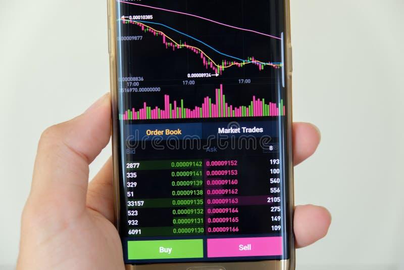 Écran de graphique du marché de StampCryptocurrency de date sur l'achat de smartphone et le bouton et la main de vente avec le fo images libres de droits