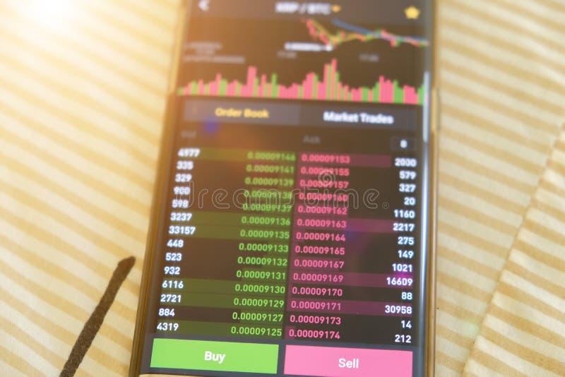 Écran de graphique du marché de StampCryptocurrency de date sur l'achat de smartphone et le bouton et la main de vente avec le fo photo stock