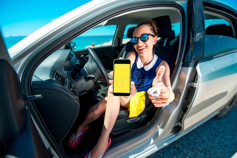 Écran de téléphone d'apparence de femme dans la voiture image libre de droits