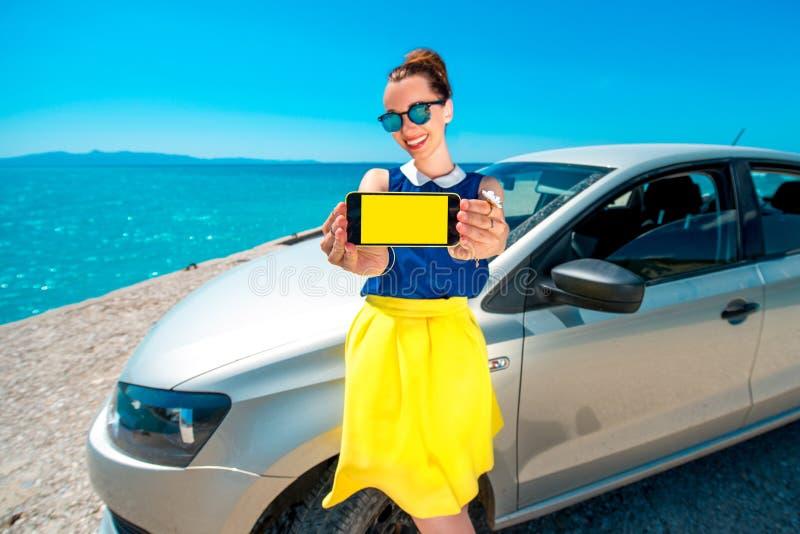 Écran de téléphone d'apparence de femme près de la voiture photos libres de droits