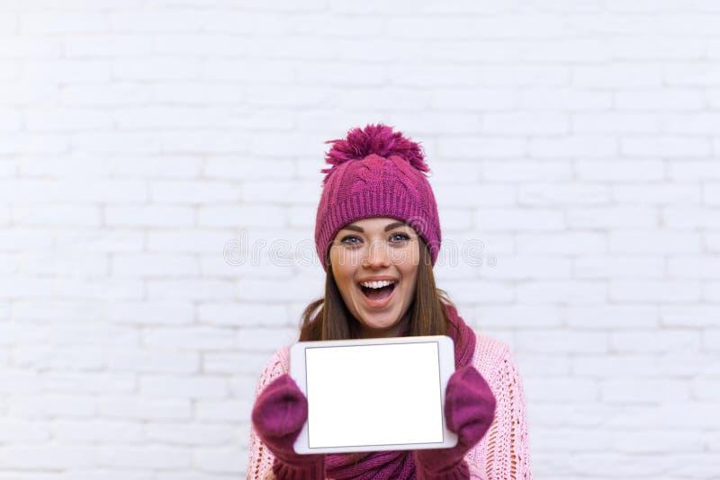Écran de tablette attrayant d'exposition d'adolescente avec l'espace vide de copie photo libre de droits