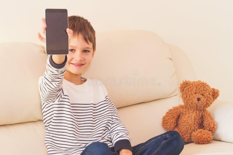 Écran intelligent de téléphone de cellules d'exposition de petit garçon avec l'espace vide de copie image stock