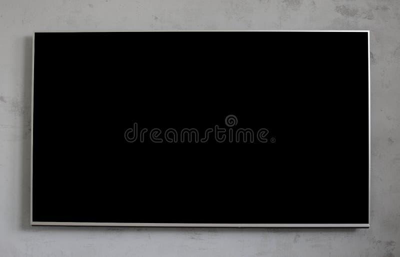 Écran noir vide de télévision sur le mur en béton photographie stock libre de droits