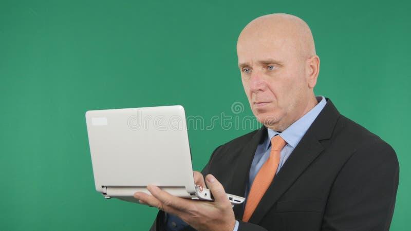 Écran sûr de vert de Working With Laptop d'homme d'affaires à l'arrière-plan photo stock