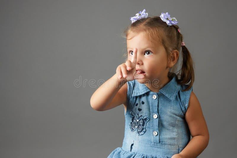 Écran tactile mignon de petite fille Fond gris photographie stock libre de droits