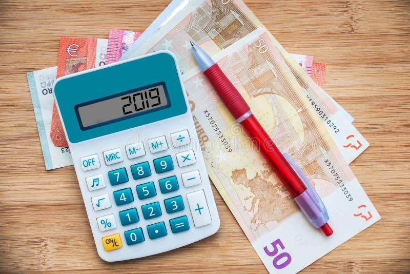 2019 écrit sur une calculatrice et des billets de banque d'euros sur le fond en bois photographie stock libre de droits