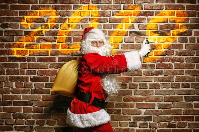 Écriture étonnée de Santa Claus sur un mur de briques peint images libres de droits