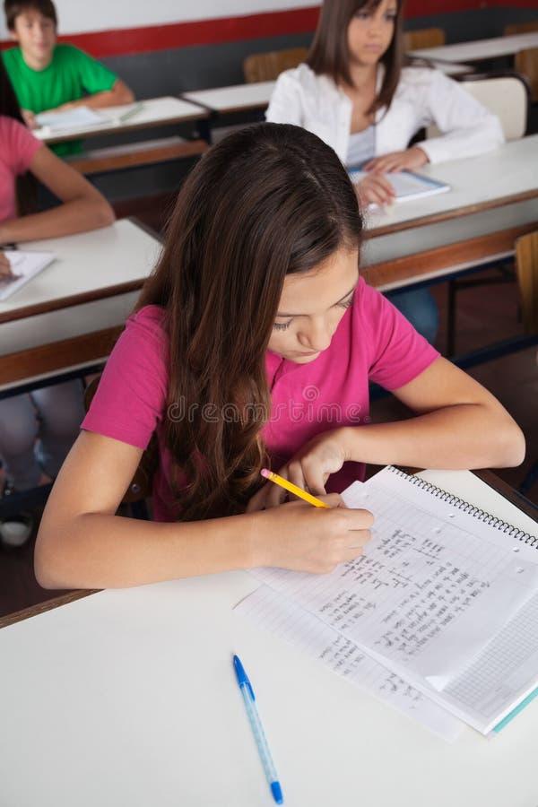 Écriture adolescente d'écolière au bureau images libres de droits