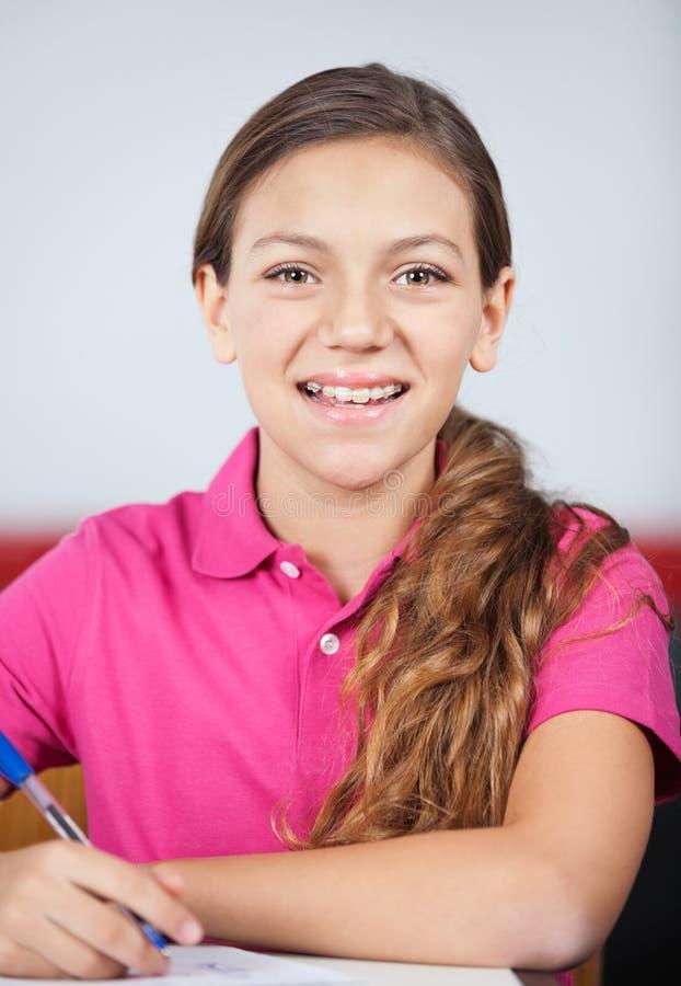 Écriture adolescente heureuse d'écolière au bureau photos stock