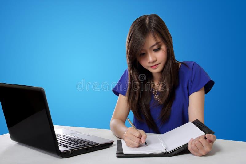 Écriture asiatique de fille d'étudiant sur le carnet, sur le fond bleu photos stock