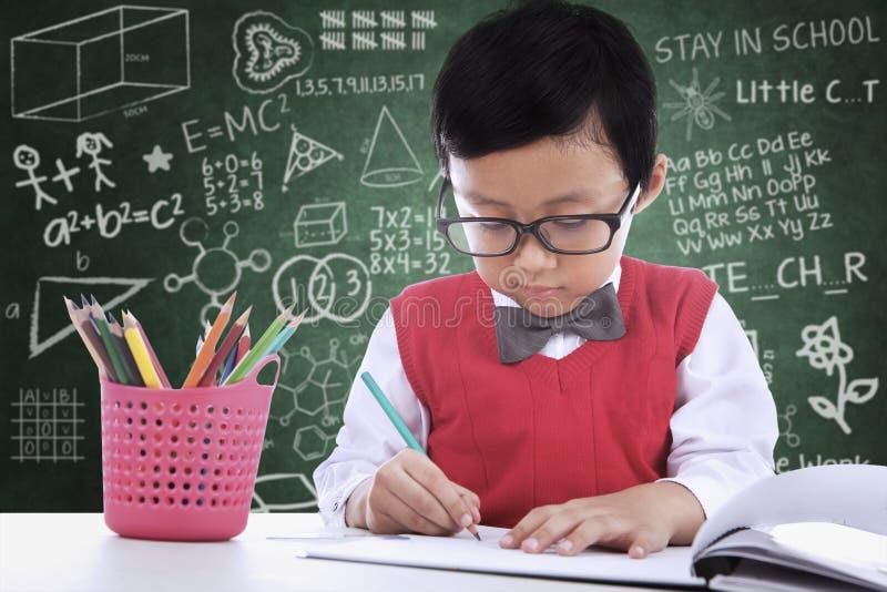Écriture asiatique de garçon d'étudiant sur le papier dans la classe image stock