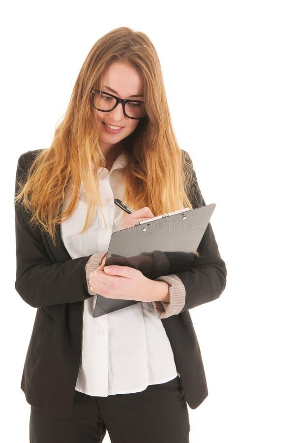 Écriture blonde de femme d'affaires sur le presse-papiers photo libre de droits