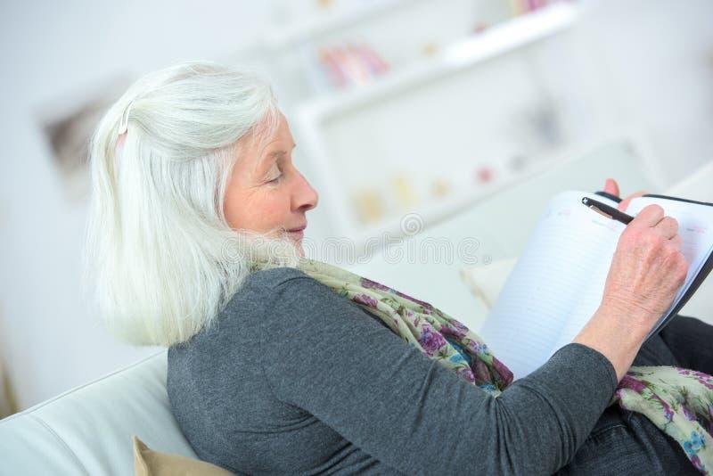 Écriture blonde mûre de femme sur le carnet image stock