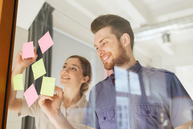 Écriture créative heureuse d'équipe sur des autocollants au bureau image libre de droits