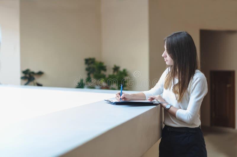 Écriture d'étudiant de brune de fille dans le carnet photographie stock