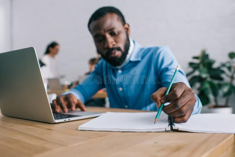 écriture d'homme d'affaires d'afro-américain dans le manuel et l'ordinateur portable d'utilisation à la table et aux collègues images stock