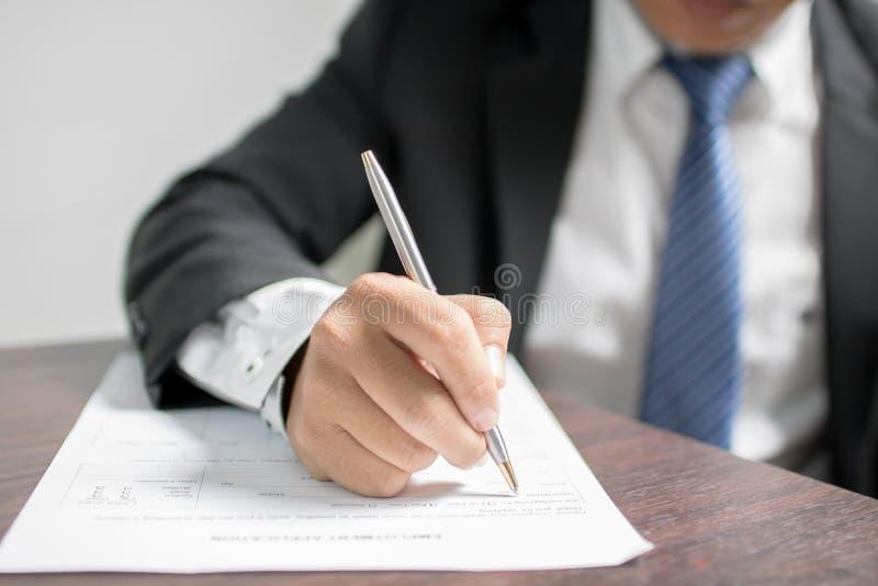 Écriture d'homme d'affaires sur le formulaire de demande et l'intervie de attente image stock