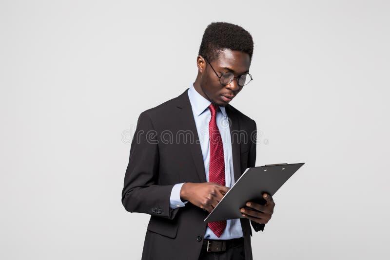 Écriture d'homme d'affaires d'afro-américain sur un presse-papiers sur le gris photos stock