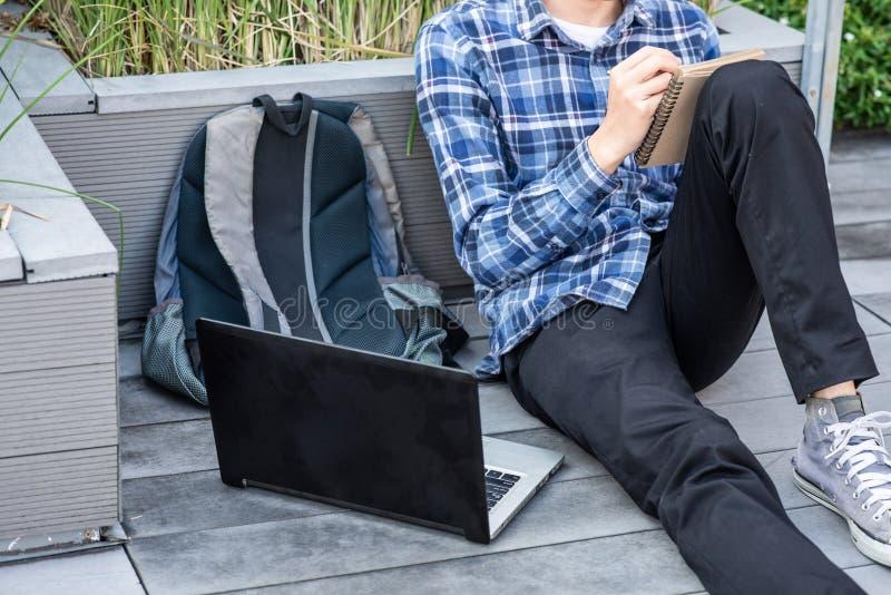 Écriture d'homme sur le livre et travailler sur l'ordinateur portable photographie stock libre de droits