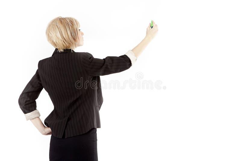 Écriture de femme d'affaires à bord photos stock