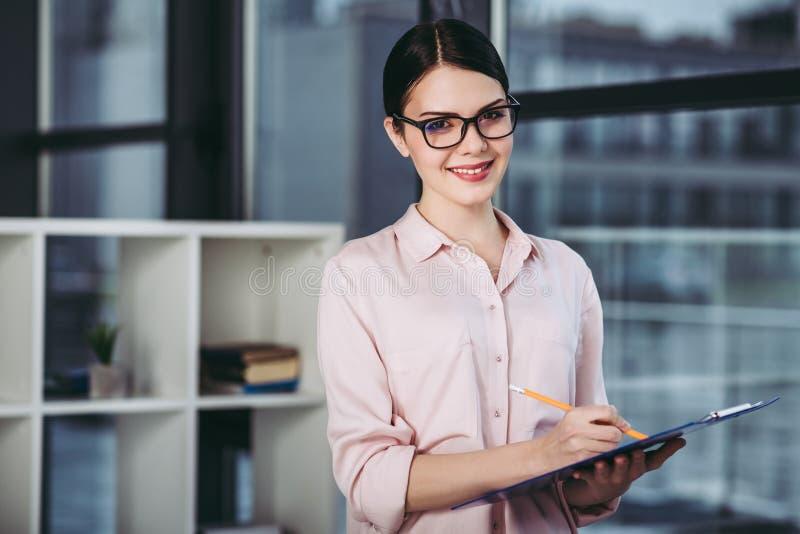 Écriture de femme d'affaires sur le presse-papiers photographie stock