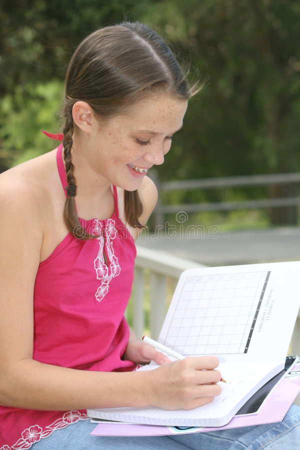 Écriture de fille d'école dans le cahier à l'extérieur images libres de droits