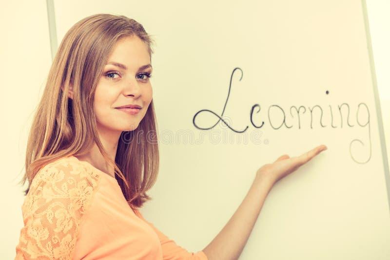 Écriture de fille d'étudiant apprenant le mot sur le tableau blanc photographie stock