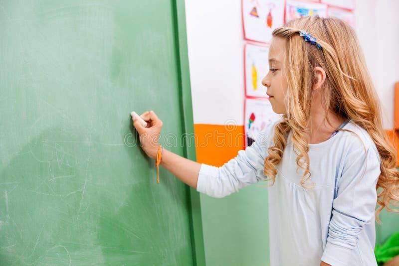 Écriture de fille sur le tableau vert dans le jardin d'enfants image stock