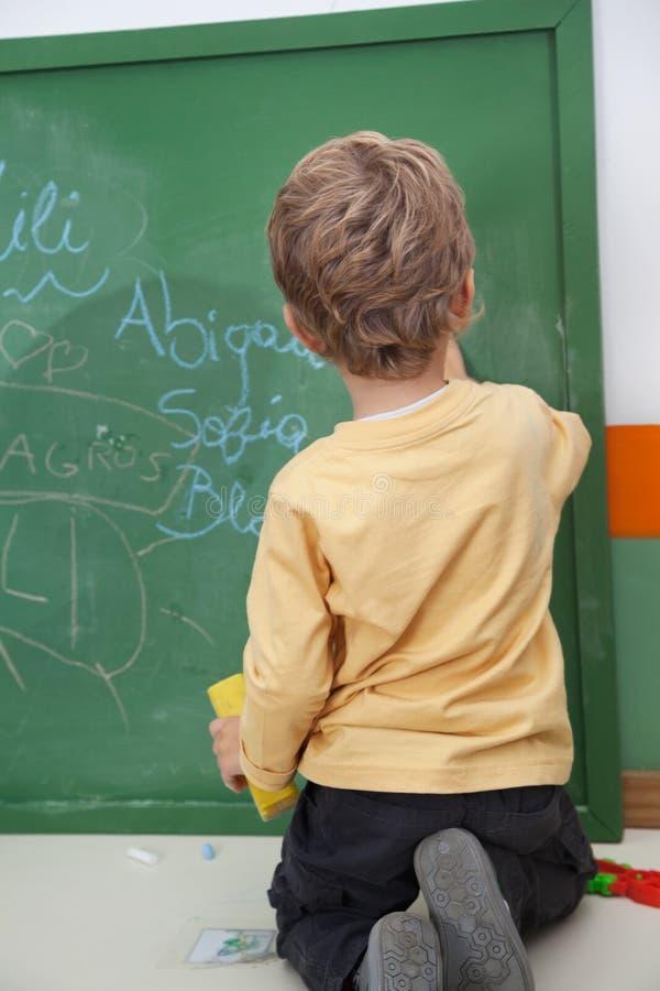 Écriture de garçon sur le tableau au jardin d'enfants images stock