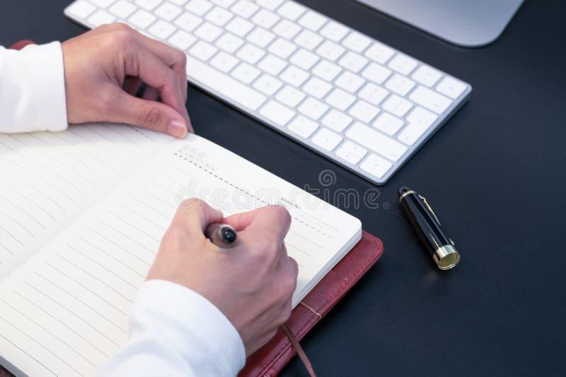 Écriture de jeune femme dans le carnet sur l'ordinateur de bureau et le clavier placés sur le bureau fonctionnant réserve vieux d images libres de droits