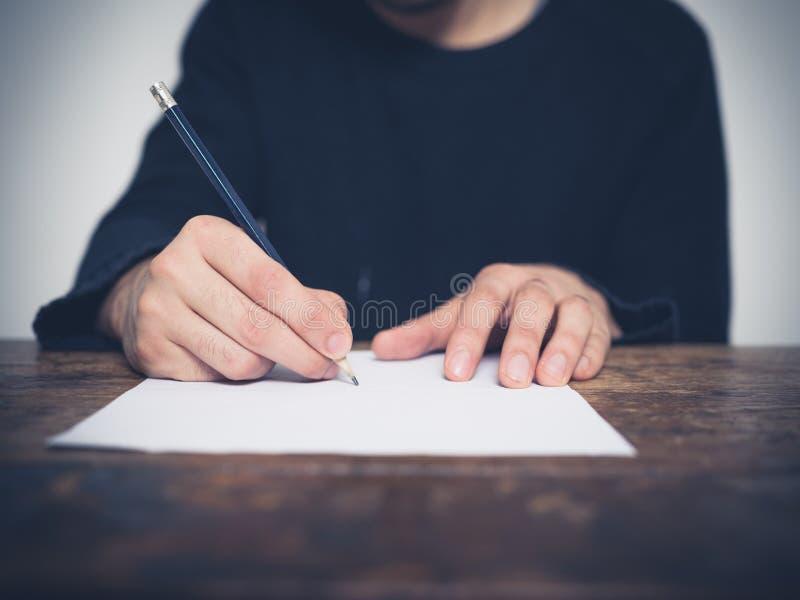 Écriture de jeune homme à la table photo stock