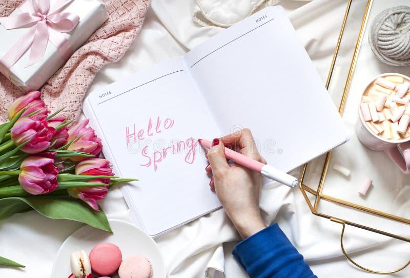 Écriture de la main de la femme dans un carnet dans un concept de lit à plat étendu avec des fleurs et une tasse de café photos libres de droits