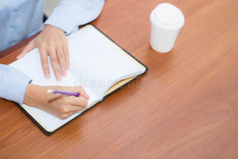 Écriture de main de femme de plan rapproché sur le carnet sur la table en bois, travail de fille avec le papier au café photos libres de droits