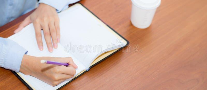 Écriture de main de femme de site Web de bannière de plan rapproché sur le carnet sur la table en bois, travail de fille avec le  images libres de droits