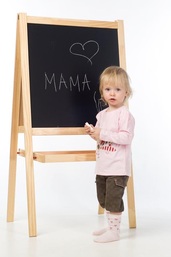 Écriture de petite fille sur un tableau noir image libre de droits