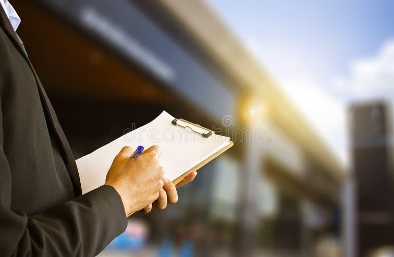 Écriture de port de costume d'homme d'affaires sur le bloc-notes et le fond trouble métaphore aux affaires à l'étude, succès, ent photos libres de droits