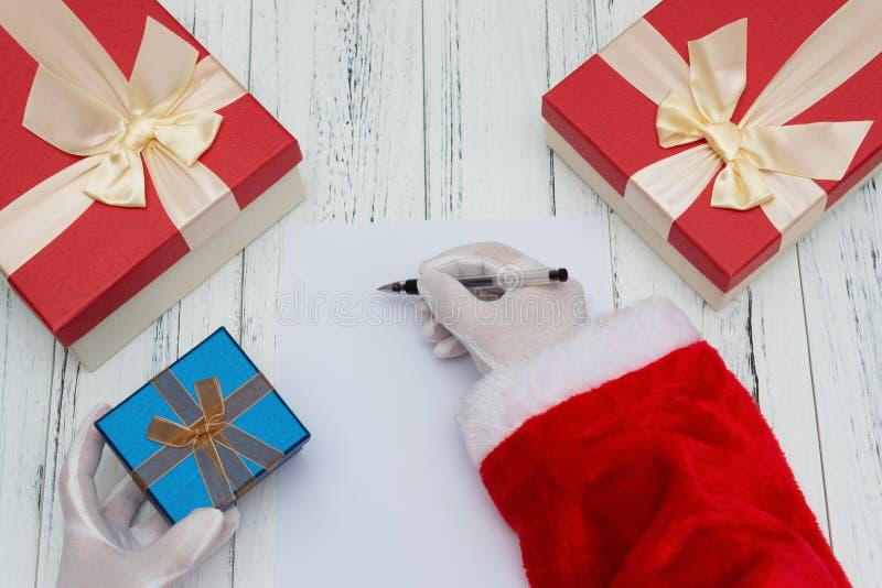 Écriture de Santa Claus sur un papier blanc bon pour la lettre ou la publicité et une main d'onher de boîte-cadeau image libre de droits