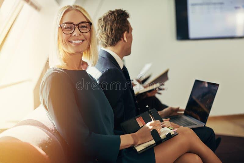 Écriture de sourire de femme d'affaires dans un carnet pendant un bureau pré image stock