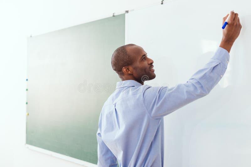 Écriture de sourire de professeur d'afro-américain sur le conseil blanc photos stock
