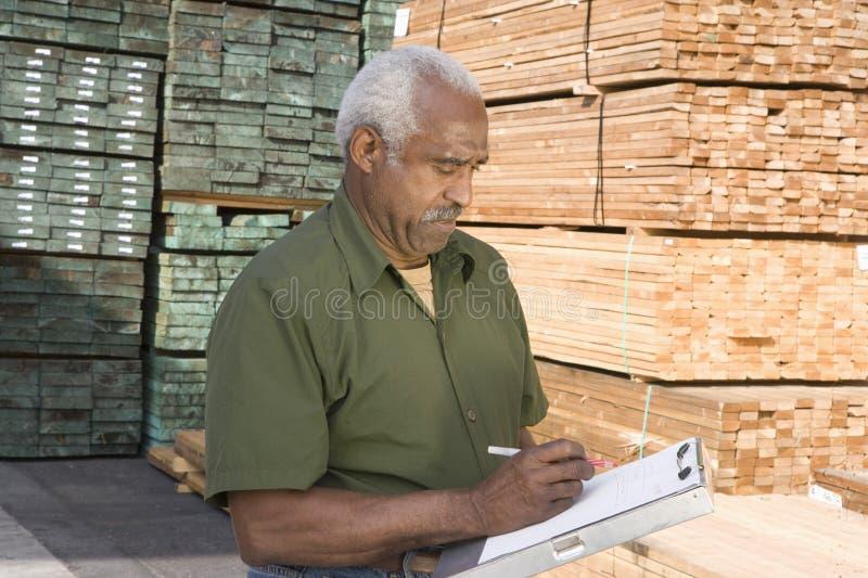 Écriture de travailleur d'entrepôt sur un presse-papiers photographie stock libre de droits