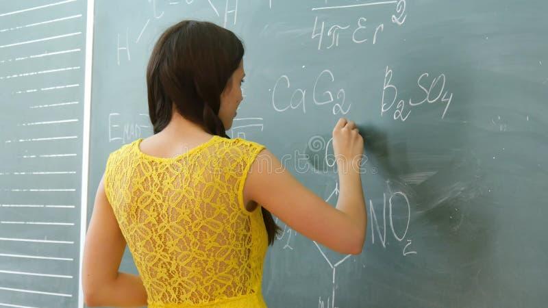 Écriture femelle assez jeune d'étudiant universitaire sur le tableau noir de tableau pendant une classe de chimie photos libres de droits