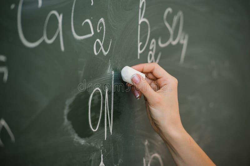 Écriture femelle assez jeune d'étudiant universitaire sur le tableau noir de tableau pendant une classe de chimie images libres de droits