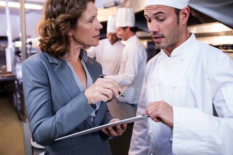 Écriture femelle de directeur de restaurant sur le presse-papiers tout en agissant l'un sur l'autre au chef principal image stock