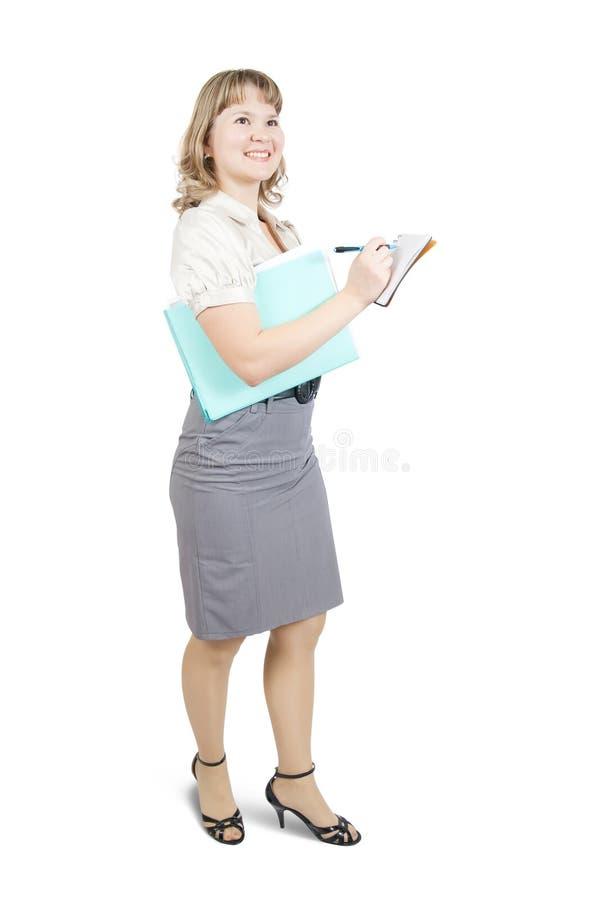 Écriture femelle de gestionnaire sur un cahier au-dessus de blanc photographie stock