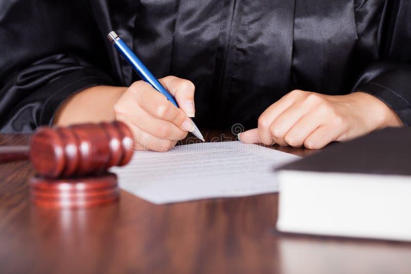 Écriture femelle de juge sur le papier image stock