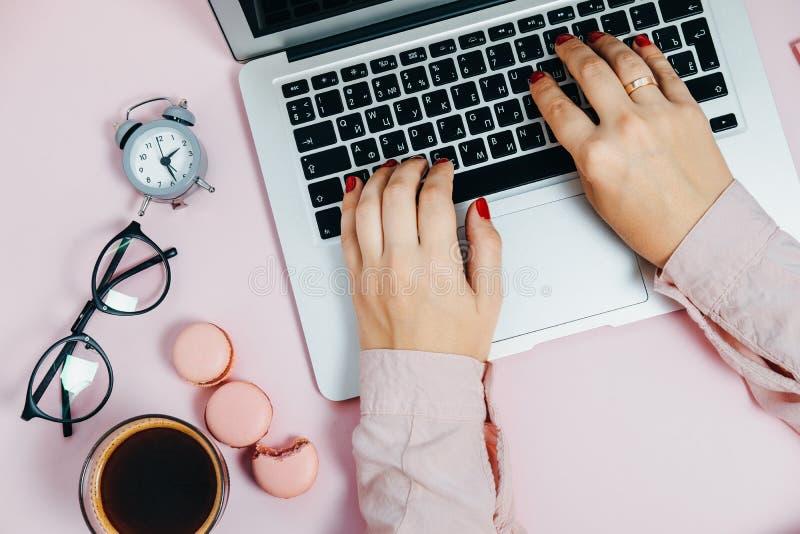 Écriture femelle de main de configuration plate sur l'ordinateur portable sur les macarons roses a d'usine photo libre de droits